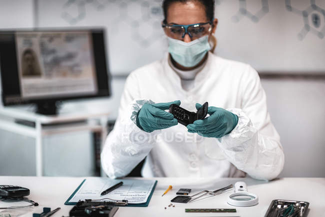 Police forensic expert examining confiscated mobile phone in science laboratory. — Stock Photo