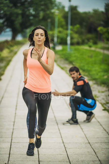 Young woman exercising running marathon in park with personal trainer. — Stock Photo