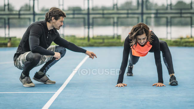 Young sporty woman exercising outdoors with personal fitness trainer. — Stock Photo