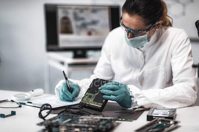 Женщина-эксперт-криминалист, изучающая жесткий диск компьютера и делающая заметки в лаборатории полиции . — стоковое фото