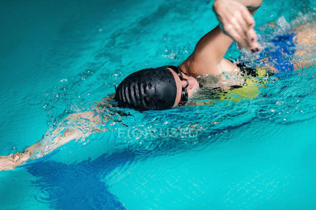 Female athlete swimming in indoor pool water. — Stock Photo