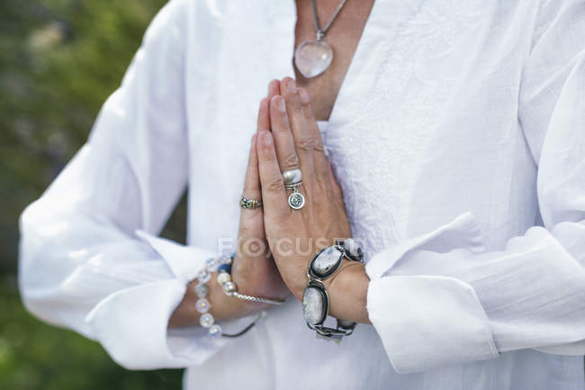 Close-up of female hands in prayer position, self-care practice for wellbeing. — Stock Photo
