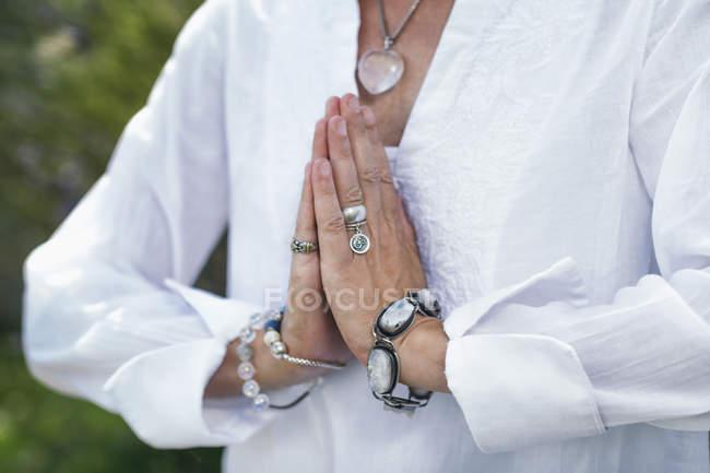 Cierre de las manos femeninas en posición de oración, autoasistencia para el bienestar.. - foto de stock
