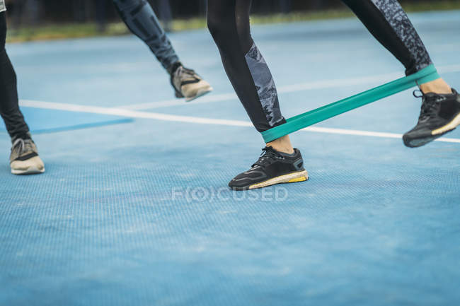 Legs of sporty female exercising with resistance band with personal fitness coach outdoors. — Stock Photo