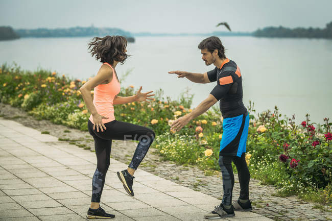Young woman exercising and lifting legs by river with personal trainer. — Stock Photo