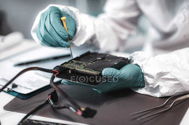 Female digital forensic expert examining computer hard drive in police science laboratory. — Stock Photo