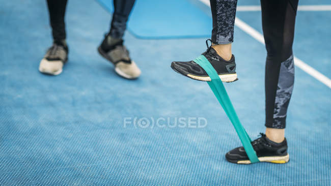 Feet of sporty female exercising with resistance band with personal fitness coach outdoors. — Stock Photo