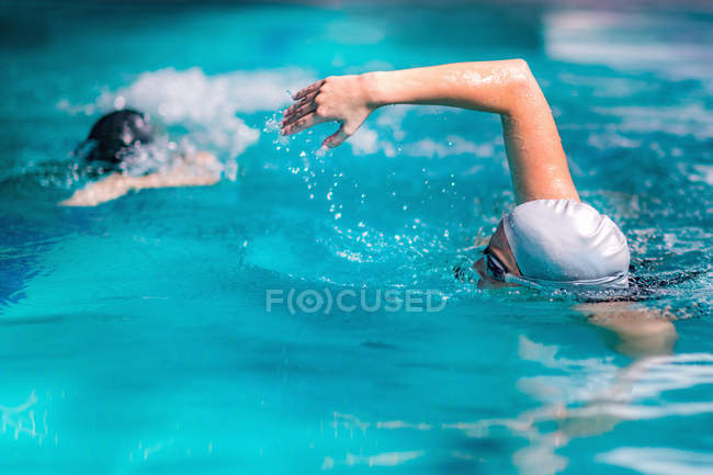 Women swimming together in indoor swimming pool. — Stock Photo