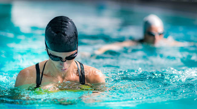 Female athletes breaststroke swimming in indoor pool. — Stock Photo