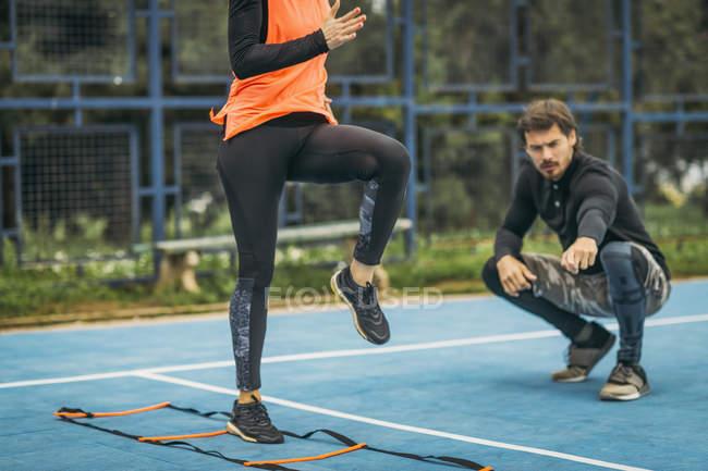 Спортивная женщина, занимающаяся с личным тренером по фитнесу с помощью лестницы ловкости . — стоковое фото