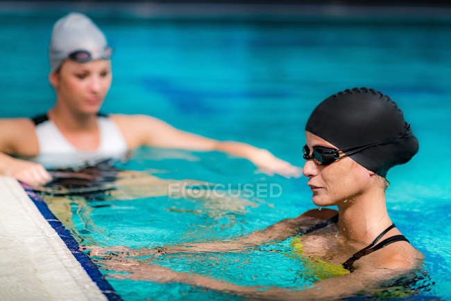 Young female swimmers swimming at poolside of indoor pool. — Stock Photo
