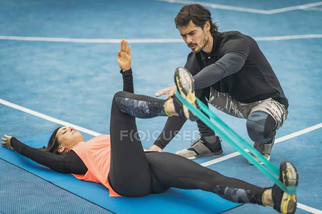 Персональный тренер по фитнесу, тренирующий молодую женщину делать упражнения на ногах . — стоковое фото