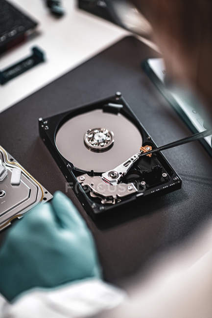 Close-up of digital forensic expert examining computer hard drive in police science laboratory. — Stock Photo