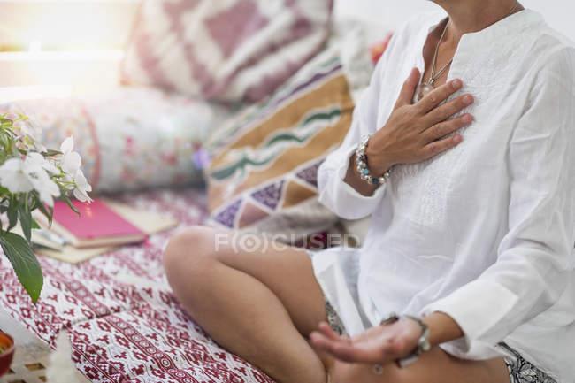 Donna seduta in posizione loto con mano destra sul chakra del cuore e palmo sinistro aperto a ricevere gesto. — Foto stock