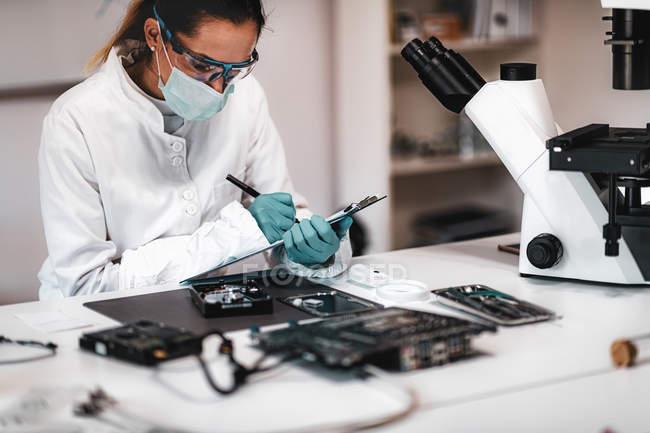 Digitaler Kriminaltechniker macht sich Notizen bei der Untersuchung der Computer-Festplatte. — Stockfoto