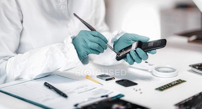 Kriminaltechniker der Polizei untersucht beschlagnahmtes Handy im Wissenschaftslabor. — Stockfoto