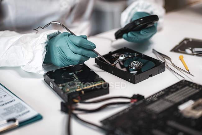 Digitale Gerichtsmedizinerin untersucht Computerfestplatte mit elektronischen Geräten im polizeiwissenschaftlichen Labor. — Stockfoto