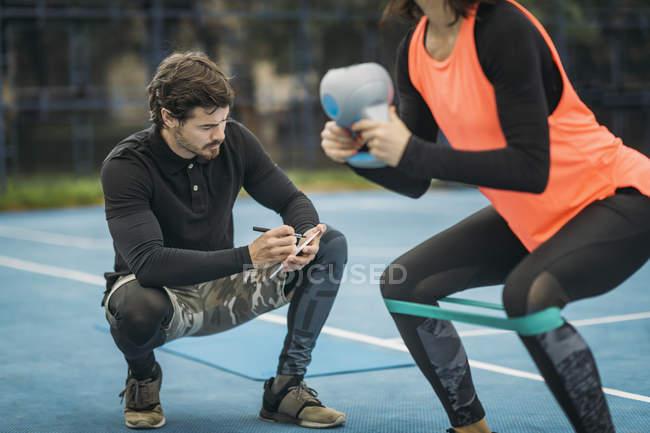 Персональный тренер по фитнесу работает с женщиной, занимающейся гиревым спортом на открытом воздухе . — стоковое фото