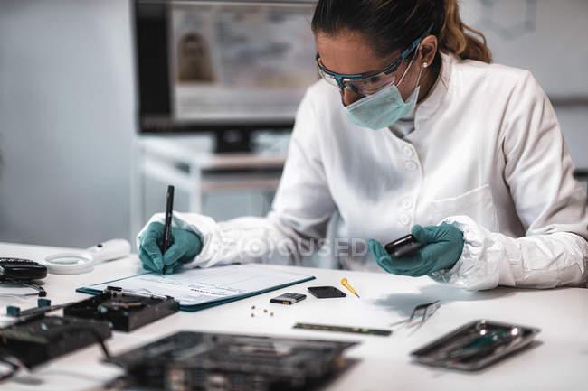 Судебный эксперт полиции делает записи во время осмотра конфискованного мобильного телефона . — стоковое фото