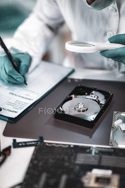 Technicien en criminalistique numérique examinant le disque dur de l'ordinateur avec une loupe et prenant des notes en laboratoire . — Photo de stock