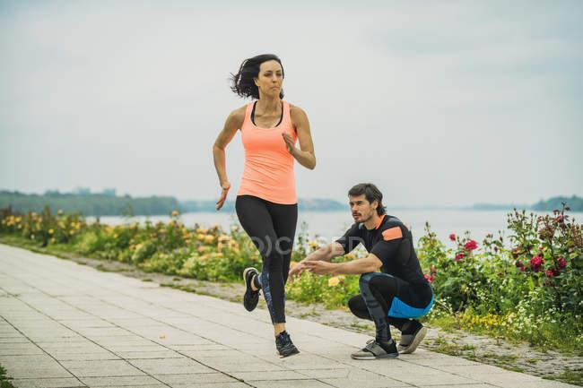 Молода жінка біжить марафоном по річці з особистим тренером.. — стокове фото