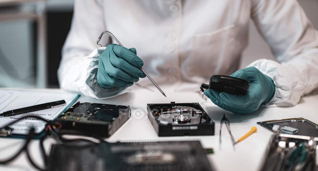 Female digital forensic expert examining computer hard drive with electronic equipment in police science laboratory. — Stock Photo