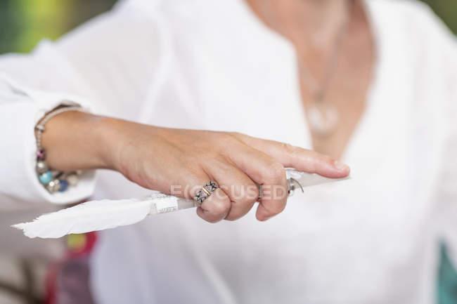 Mano di guaritrice spirituale femminile in possesso di cristallo con piuma bianca. — Foto stock