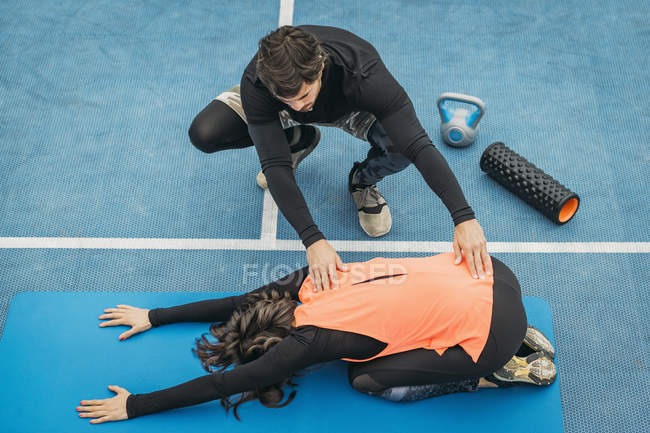 Fit young woman doing stretching exercise after training with personal fitness trainer. — Stock Photo