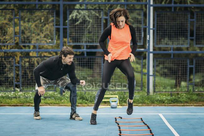 Молода жінка займається фізичними вправами з допомогою спритної драбини. — стокове фото