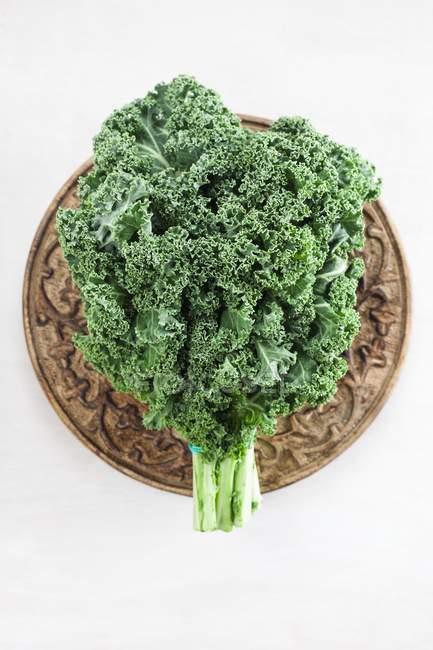 Hojas de col rizada Brassica oleracea en placa redonda de madera . - foto de stock