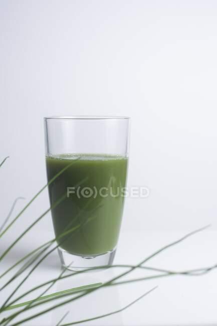 Green juice made of fresh wheatgrass on white background. — Stock Photo