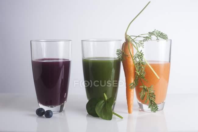 Jugos frescos hechos de bayas, zanahoria y hojas verdes . - foto de stock