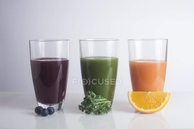 Vasos de zumos frescos hechos de bayas, naranja y col rizada . - foto de stock