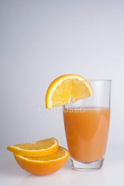 Frisch gepresster Orangensaft und Orangenscheiben. — Stockfoto