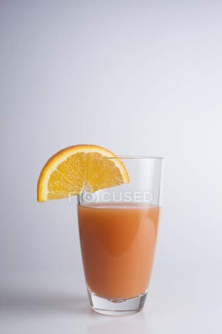 Freshly squeezed orange juice in glass and orange slice. — Stock Photo