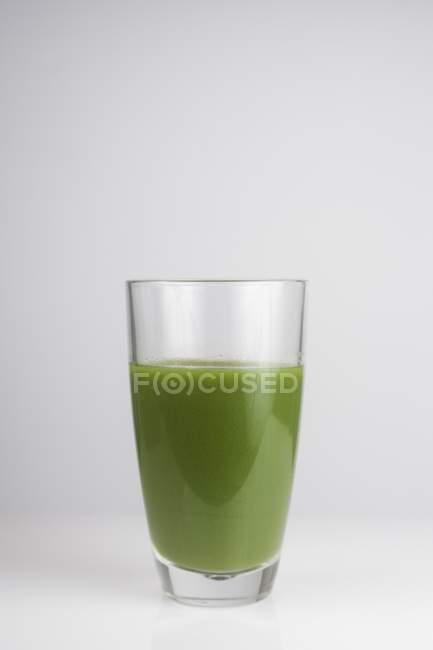 Verre de jus vert antioxydant frais, prise studio. — Photo de stock