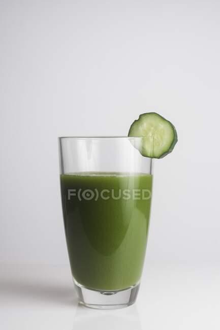 Un vaso de jugo verde fresco con una rebanada de pepino . - foto de stock