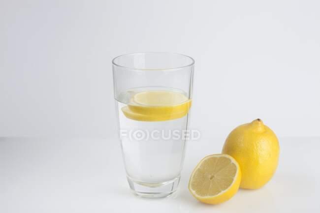 Скло органічної води з свіжими лимонними скибками.. — стокове фото