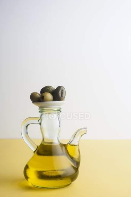 Jarra de aceite de oliva con aceitunas en la mesa, toma de estudio . - foto de stock