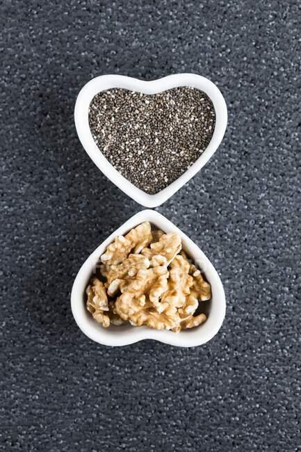Чорне насіння чії та волоські горіхи у стравах у формі серця.. — стокове фото