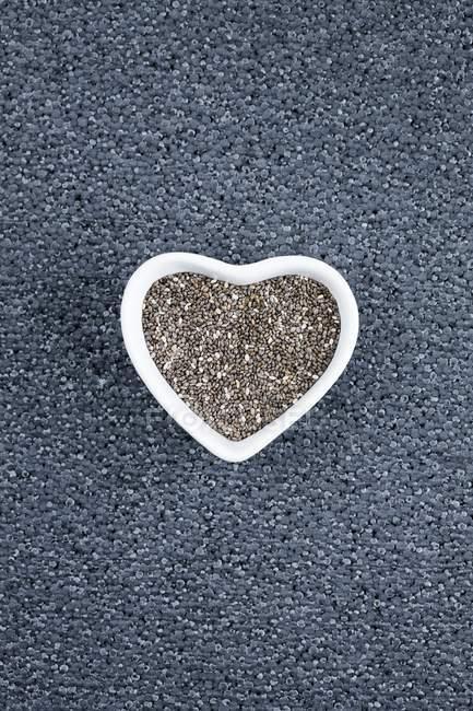 Чорне насіння шиї в серцевій тарілці, зверху на сірому фоні.. — стокове фото