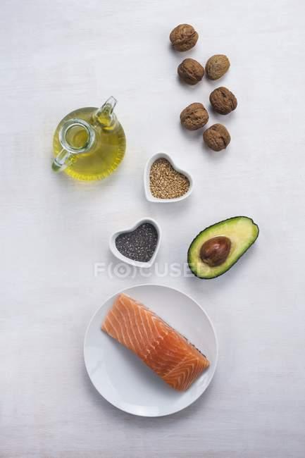 Vue du haut de divers aliments riches en oméga-3 - saumon, avocat, noix, huile d'olive et chia. — Photo de stock