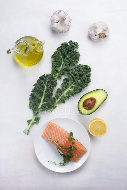 Vue du haut de divers aliments riches en oméga-3 - saumon, avocat, chou frisé, huile d'olive et ail. — Photo de stock