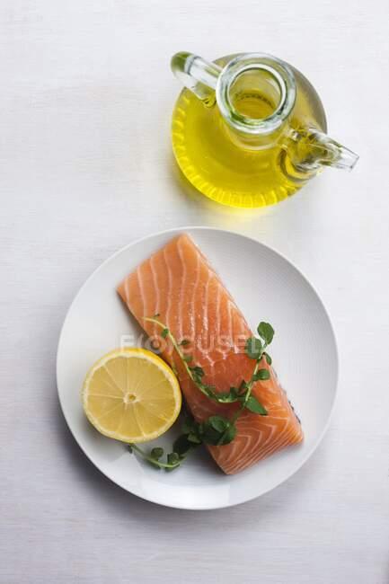 Saumon avec citron et herbes et huile d'olive, régime alimentaire sain et concept de gras monoinsaturés. — Photo de stock