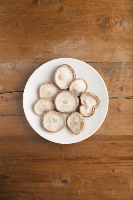 Teller mit Shiitake-Pilzen Lentinula edodes von oben auf Holztisch. — Stockfoto