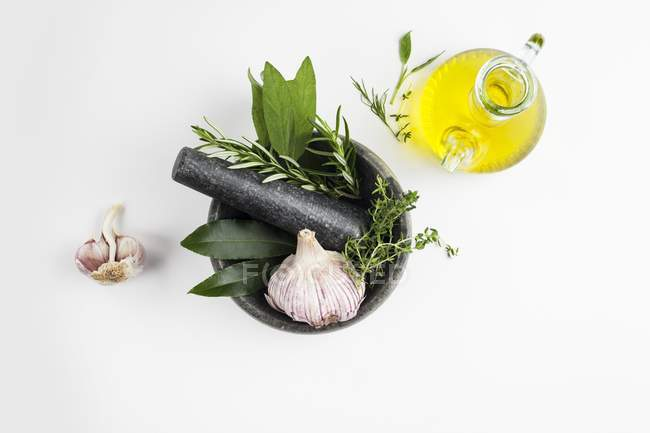 Мортира і пестик з часником і травами і оливковою олією.. — стокове фото