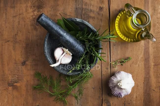 Mortero y mortero con ajo y hierbas y aceite de oliva sobre mesa de madera, vista superior . - foto de stock