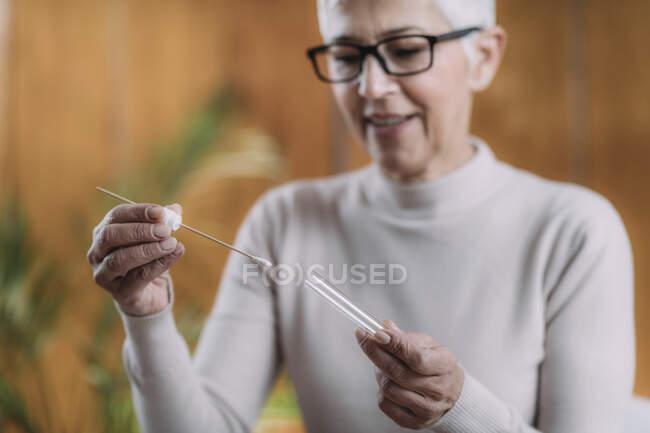 Пожилая женщина делает ДНК-тест дома. — стоковое фото