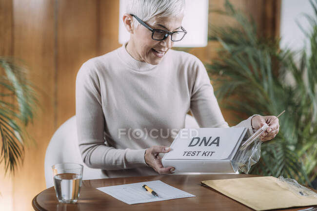 Senior woman doing a mailed DNA test at home. — Stock Photo