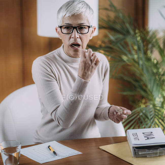 Senior woman doing a DNA test at home. — Stock Photo